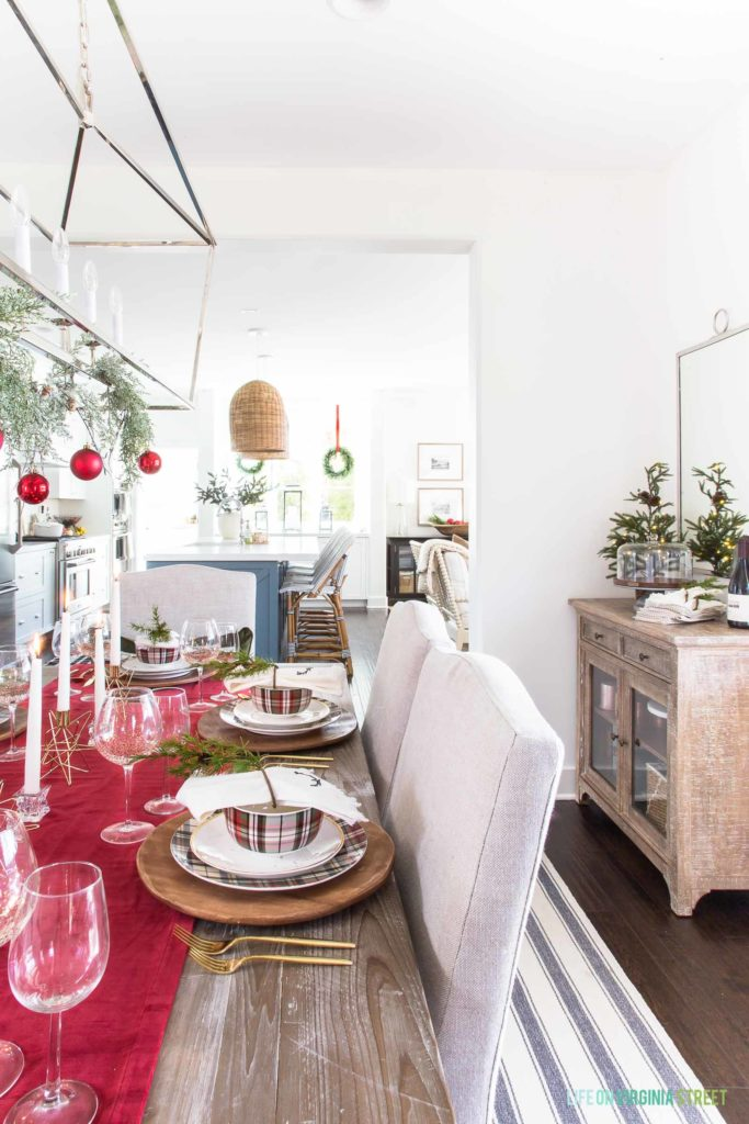 A red plaid Christmas dining room with linen chairs and reclaimed wood dining table. I love the wood chargers, plaid dishes, and gold flatware!