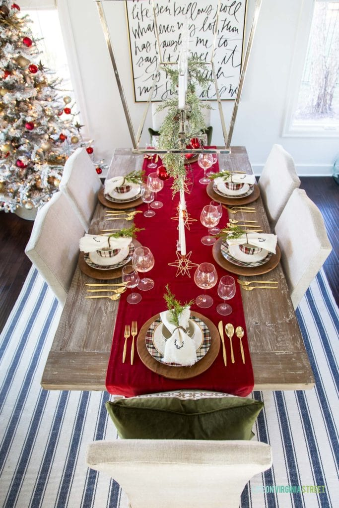 A red plaid Christmas tablescape with a velvet runner, gold flatware, wood chargers, and plaid dishes.