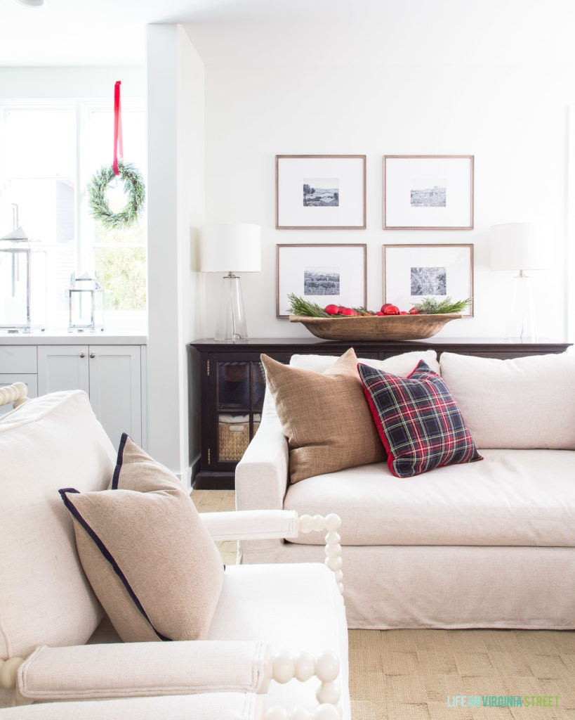 A neutral Christmas living room with white spindle chairs, a linen sofa, brown linen pillow, black and red Stewart plaid pillow, wood gallery wall, wood dough bowl filled with ornaments and greenery, and wreaths hung in the window. Such a cute Christmas family room!