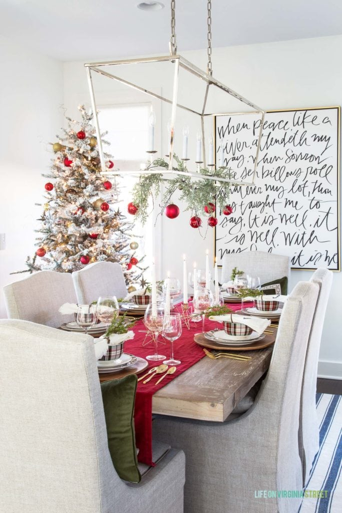 A Christmas tablescape with a red velvet runner, gold flatware and plaid plates and bowls. I love the garland and ornaments hanging from the silver chandelier!
