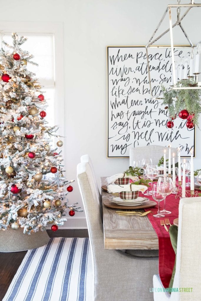 A beautiful Christmas dining room with blue and white striped rug, linen chairs, reclaimed wood table and Simply White walls. I love the red, green and plaid decor used on the tablescape!