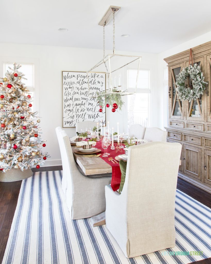 "A coastal dining room with linen chairs, reclaimed wood table, silver linear Darlana pendant light decorated with garland and red ornaments, a flocked Christmas tree and a blue and white striped rug. I love the large ""It Is Well"" canvas art on the wall!"