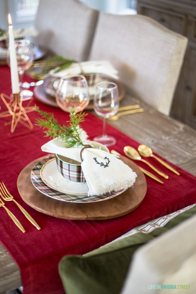 A Christmas place setting with plaid plates, gold flatware, white linen deer napkins, and faux greenery napkin rings.