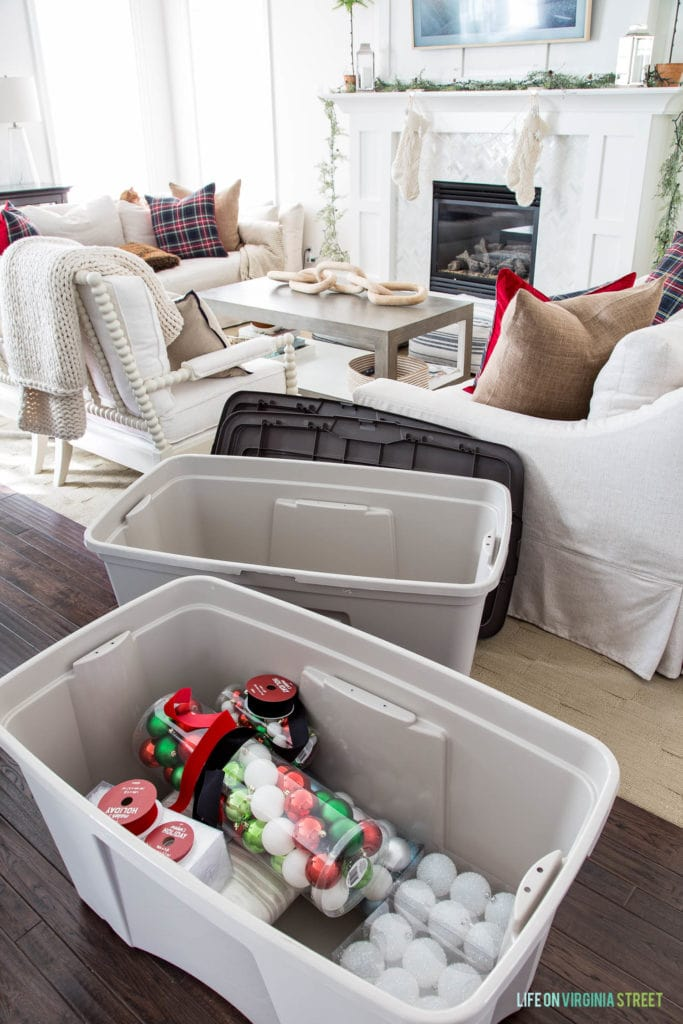 Neutral living room with Christmas ornaments in a plastic bin.