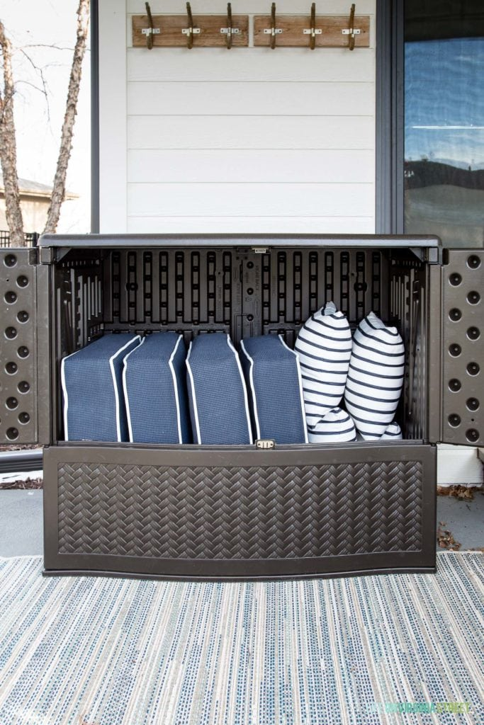 An outdoor storage cabinet with outdoor pillows in it.