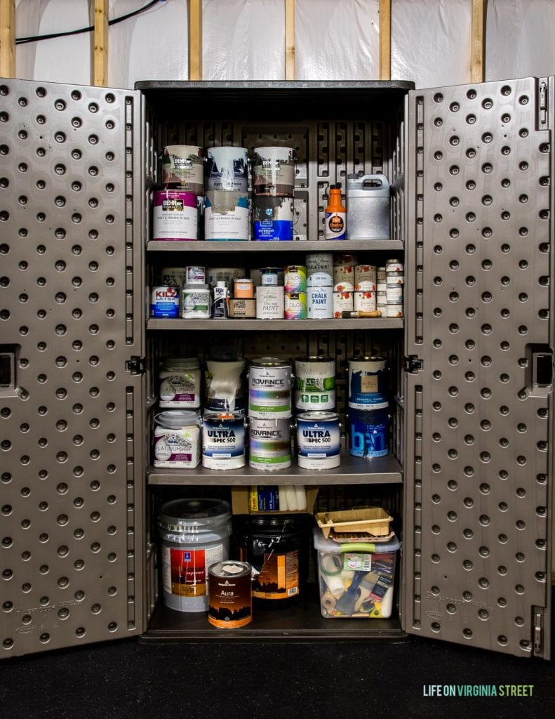 A storage cabinet filled with various sizes of paint cans.