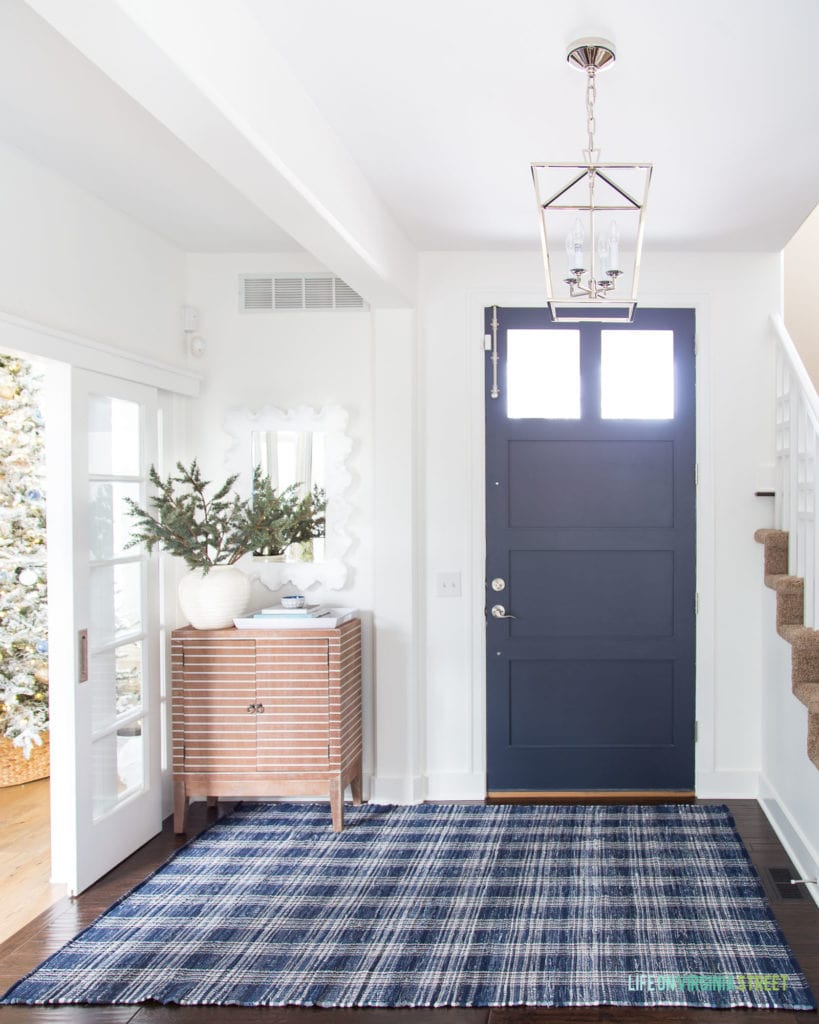 A wintery Christmas entryway with navy blue front door, white walls, a navy blue plaid rug, striped wood cabinet, silver lantern pendant light, and faux greenery. You can also see a peek of the blue and metallic flocked Christmas tree!