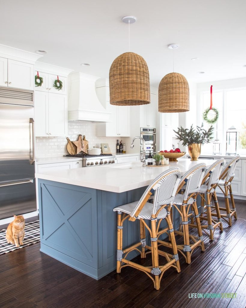 A Christmas kitchen with small wreaths on the cabinets hung with red velvet ribbons. I love the white cabinets with the white beveled subway tile, blue kitchen island, basket pendant lights, and French bistro style counter stools! The gold bowl and gold vase filled with ornaments and greenery add a festive vibe!