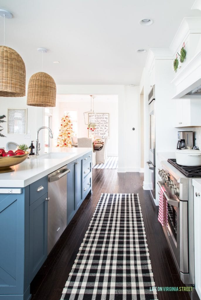 A coastal inspired kitchen with white cabinets, a blue island, black and white plaid runner rug, woven basket pendant lights, wreaths on the cabinets, and red and gold accents.