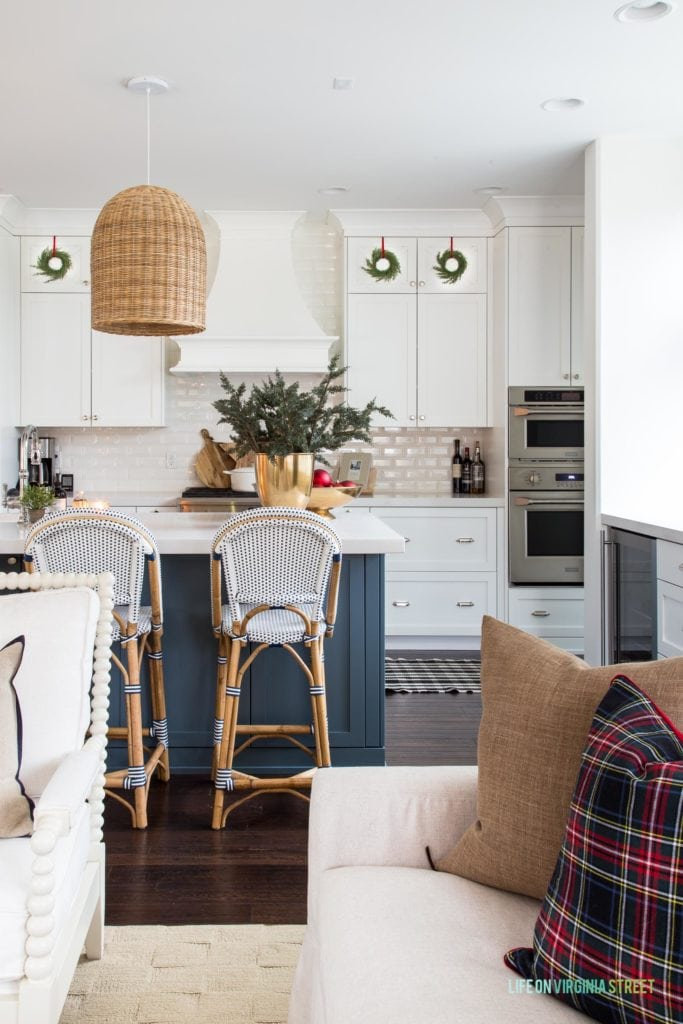 A white Christmas kitchen with blue island, wreaths on the cabinet doors, basket pendant lights, plaid pillows, bistro chairs and plaid rugs!