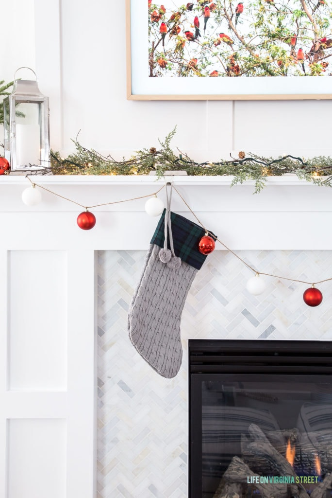 A simple Christmas mantel with a DIY ornament garland and red, white and green accents.