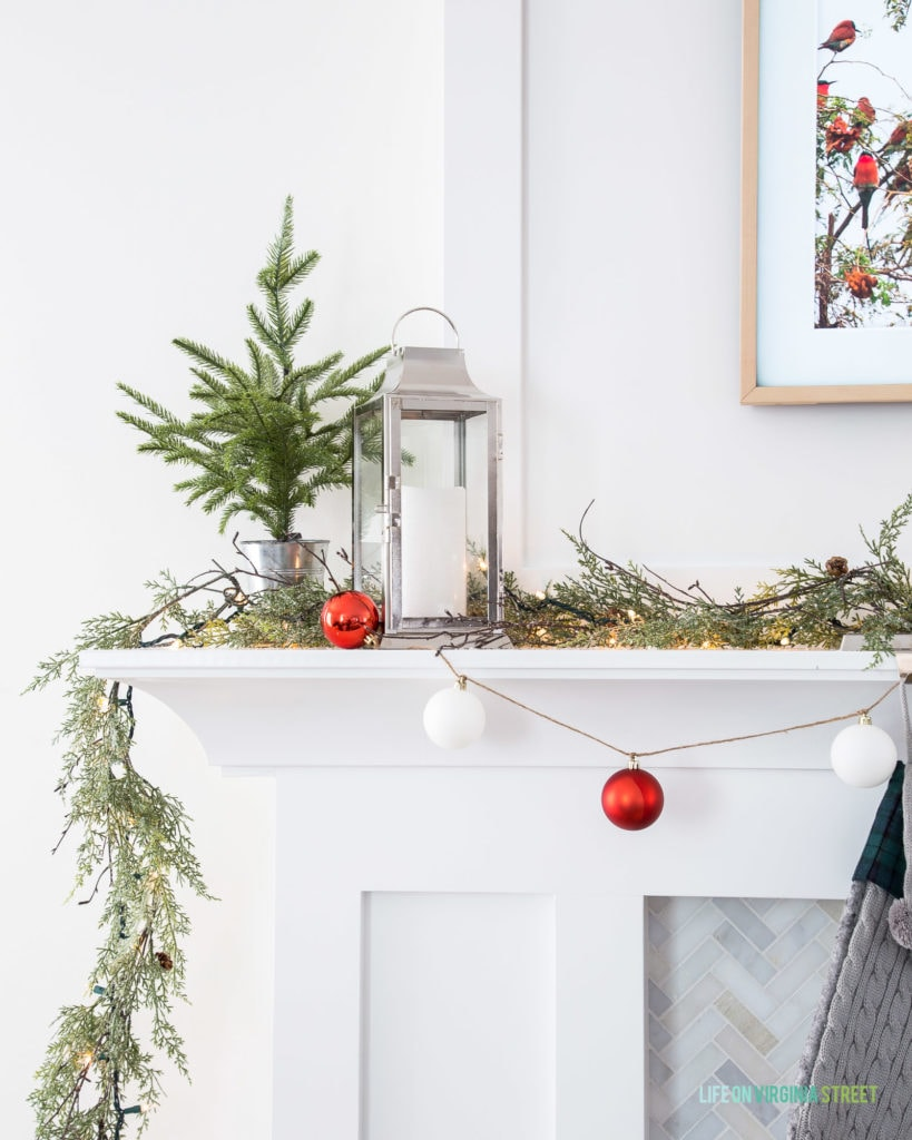 A silver lantern with a flameless flickering candle on a simple Christmas mantel.