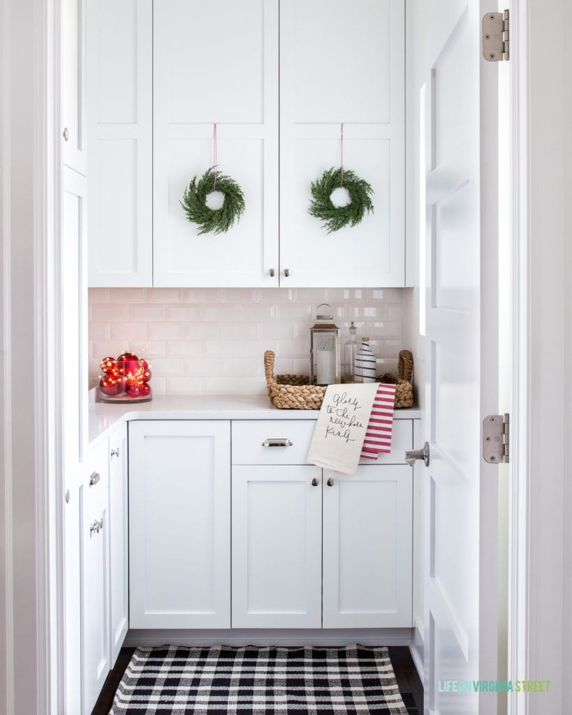 The cutest kitchen Pantry decorated for Christmas! I love the idea of cabinets in a pantry, and these mini green wreaths, black and white plaid rug, red ornaments and other festive touches are the perfect addition!