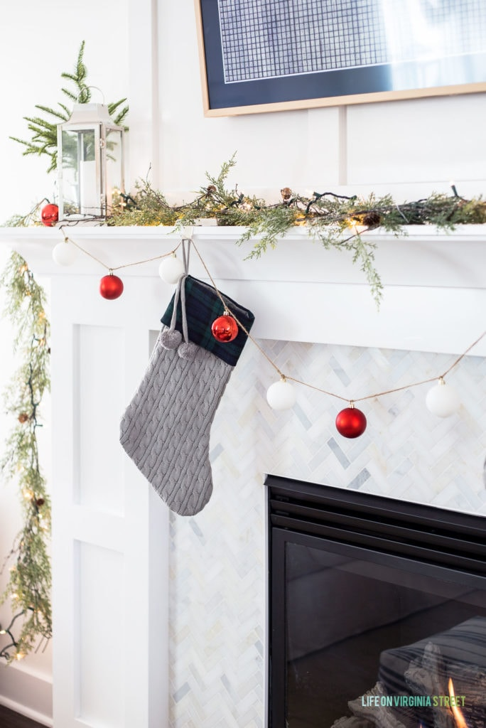 A gray cableknit and plaid stocking on a white mantel with marble herringbone tile.