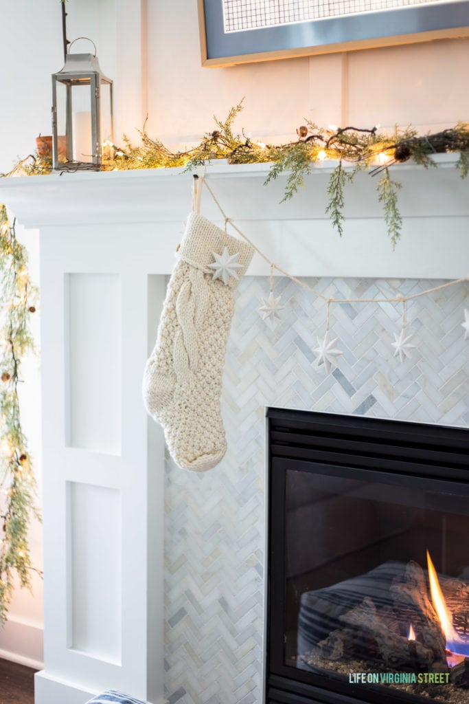 A chunky knit stocking hung on a white fireplace mantle with herringbone marble tile surround. I love the garland and lights along with the silver lantern!