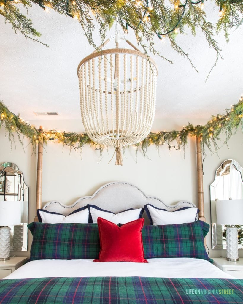 Such pretty plaid Christmas decor bedding in this holiday bedroom! I also love the white bead chandelier and the red velvet pillow on the canopy bed!