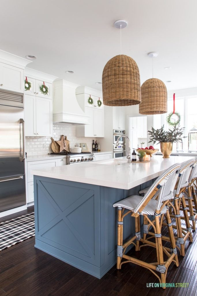 A white kitchen with a blue island, basket pendant lights, mini wreaths on cabinets, gold vase, and black and white runner. Such a cute Christmas kitchen!