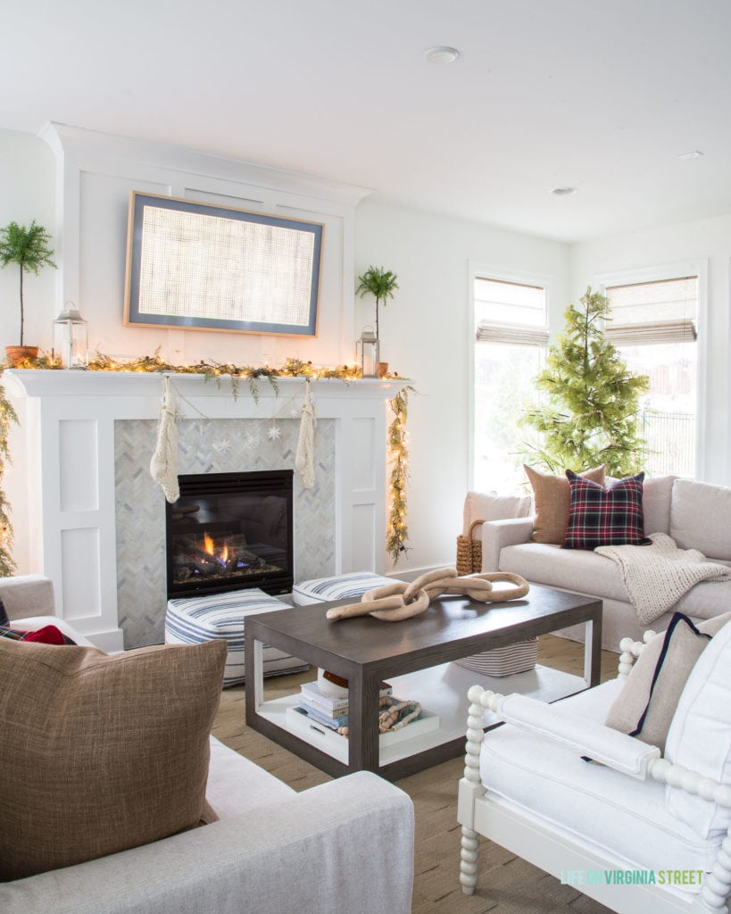 A Christmas living room with neutral linen sofa and chairs, a white mantle, and herringbone marble fireplace surround. The garland with twinkle lights, faux Cypress tree, and black Stewart plaid pillows add a fun festive touch to this family room.