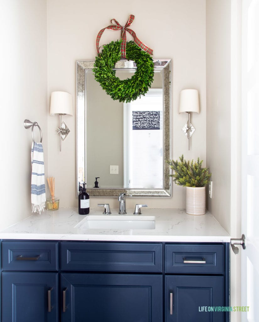 A powder bath room decorated for Christmas! I love the addition of the boxwood wreath hung with a plaid ribbon. The star sconces and navy blue cabinets make this room feel even more festive!