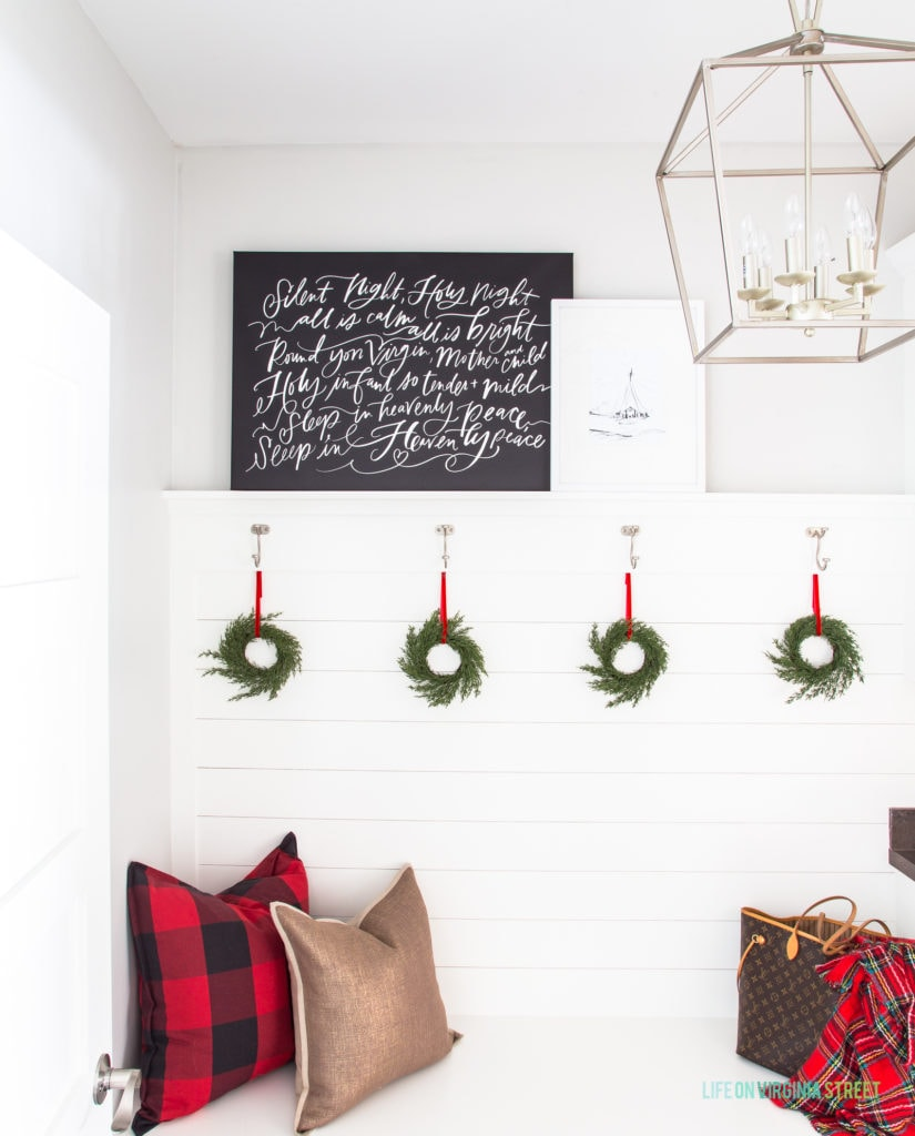 A mudroom with white shiplap walls and silver lantern pendant light. I love the red buffalo check pillow, gold pillow, black Silent Night canvas art and the wreaths for Christmas!