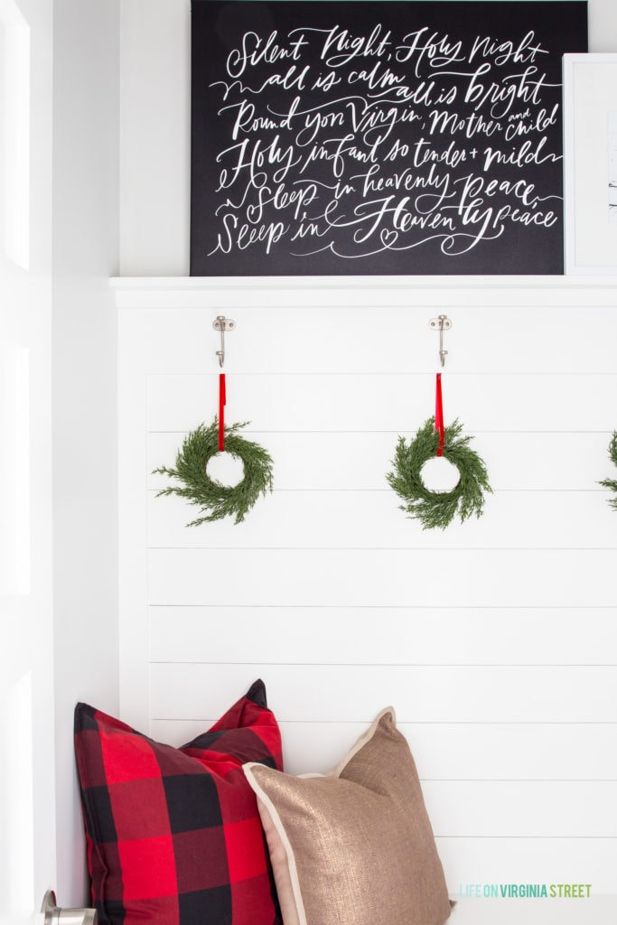 Cute Christmas decorations with buffalo check plaid pillow, a black Silent Night canvas artwork and mini green wreaths hung with red velvet ribbon.