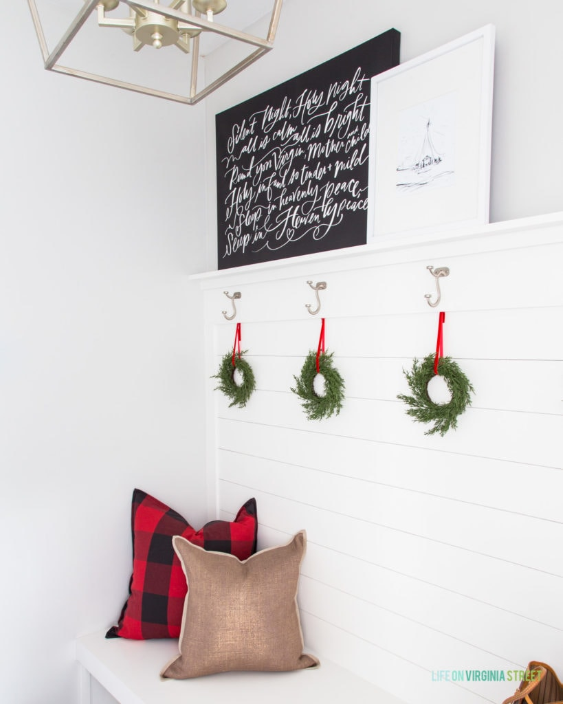 A cute mudroom decorated for Christmas! I love the half shiplap wall and hooks!