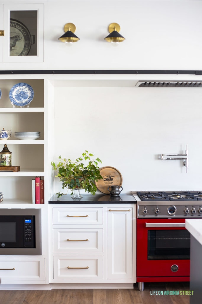 White kitchen cabinets painted Benjamin Moore Cloud Cover. The red Italian range adds a punch of color to this beautiful English Farmhouse kitchen!