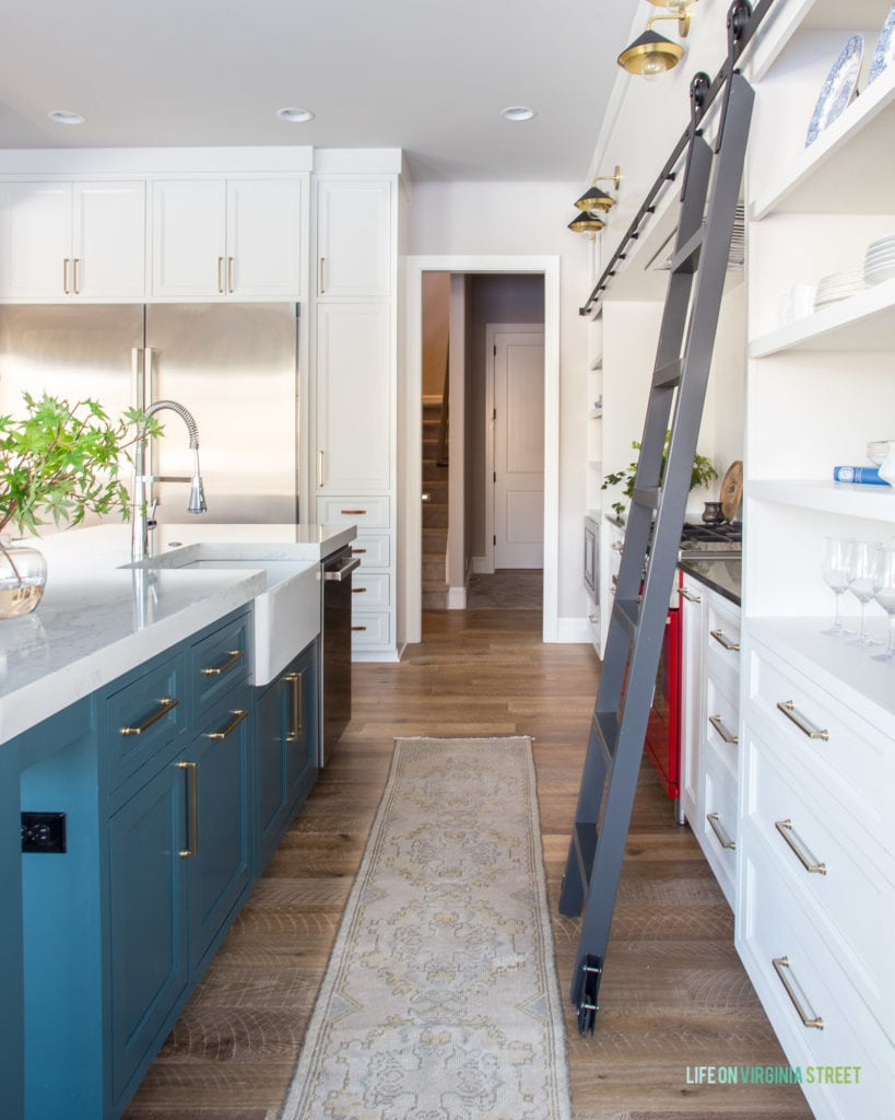 A gorgeous English farmhouse kitchen feature a blue green island (Benjamin Moore Yorkshire Greene), a vintage runner, white cabinets (Benjamin Moore Cloud Cover), and a metal library ladder!