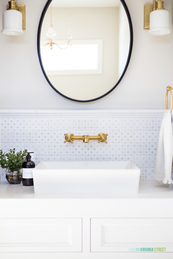 A beautiful vanity with white cabinets, blue and white patterned subway tile, iron mirror, brass sconces and gold fixtures and hardware.