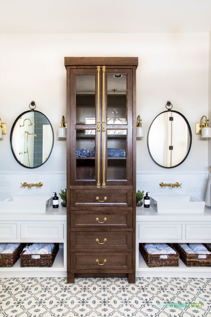 A double white vanity with walnut stained linen cabinet, oval iron mirrors, blue and white patterned backsplash tile, and gold fixtures.