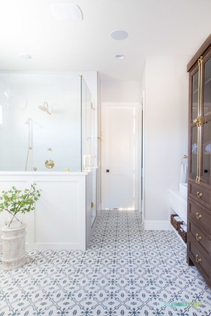 A beautiful English farmhouse bathroom with patterned tile floors, white board and batten, Benjamin Moore Collingwood walls, walnut stained bathroom cabinets, and gold fixtures.