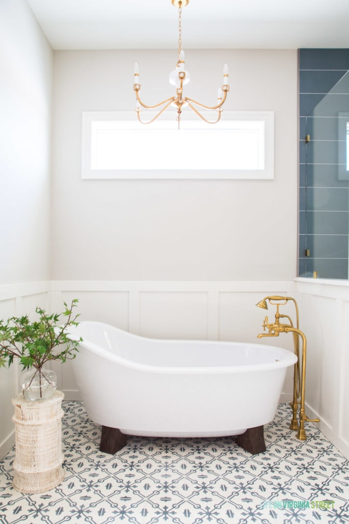 Beautiful pedestal bathtub in a English farmhouse style bathroom. The gray and white patterned floors pair beautifully with the white board and batten and gold fixtures. The walls are Benjamin Moore Collingwood.