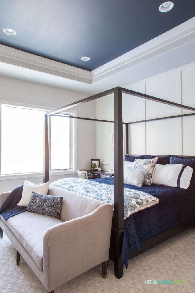 Master bedroom with white board and batten walls and a dark ceiling painted Benjamin Moore Midnight Blue.