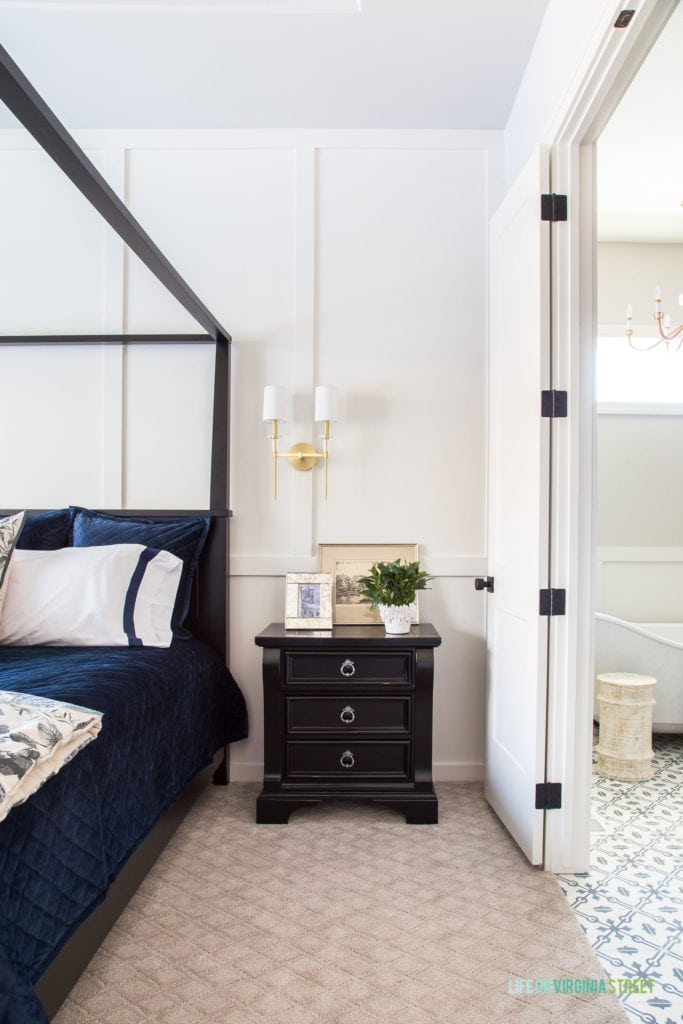 White board and batten painted Benjamin Moore Cloud Cover. Bedroom features a canopy bed, navy blue linens, and gold sconces.