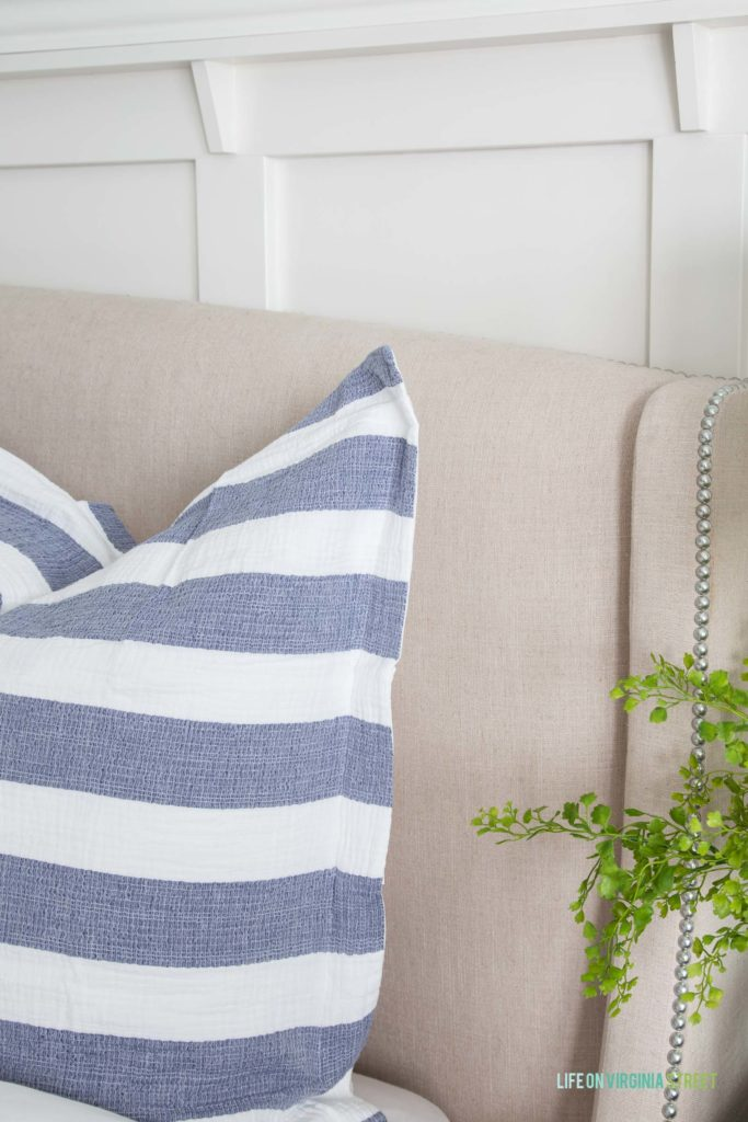 Up close picture of the blue and white striped pillows on bed.