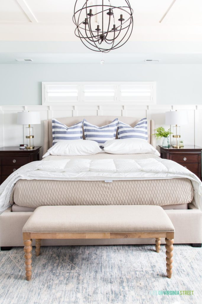 Striped blue and white pillows on bed with chandelier above the bed.