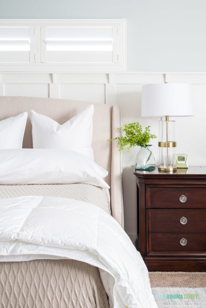 Neutral bed with white pillows and bamboo blanket.