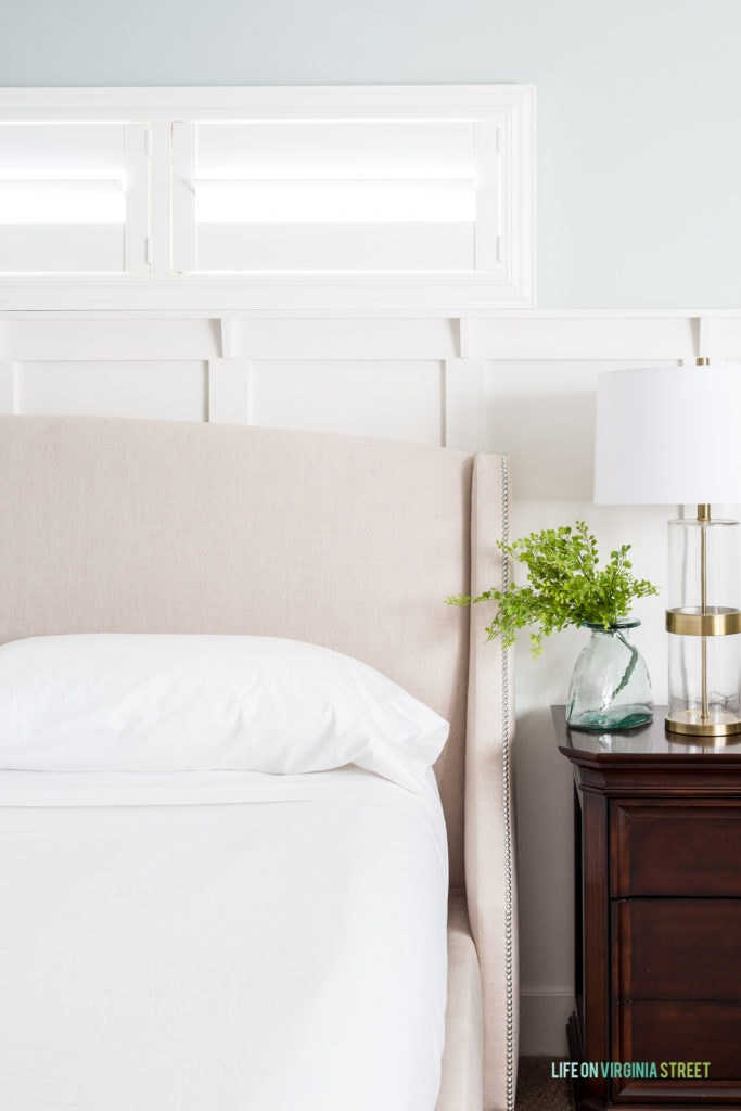 White bedding on neutral bed with a wood side table and clear glass vase with greenery in it.