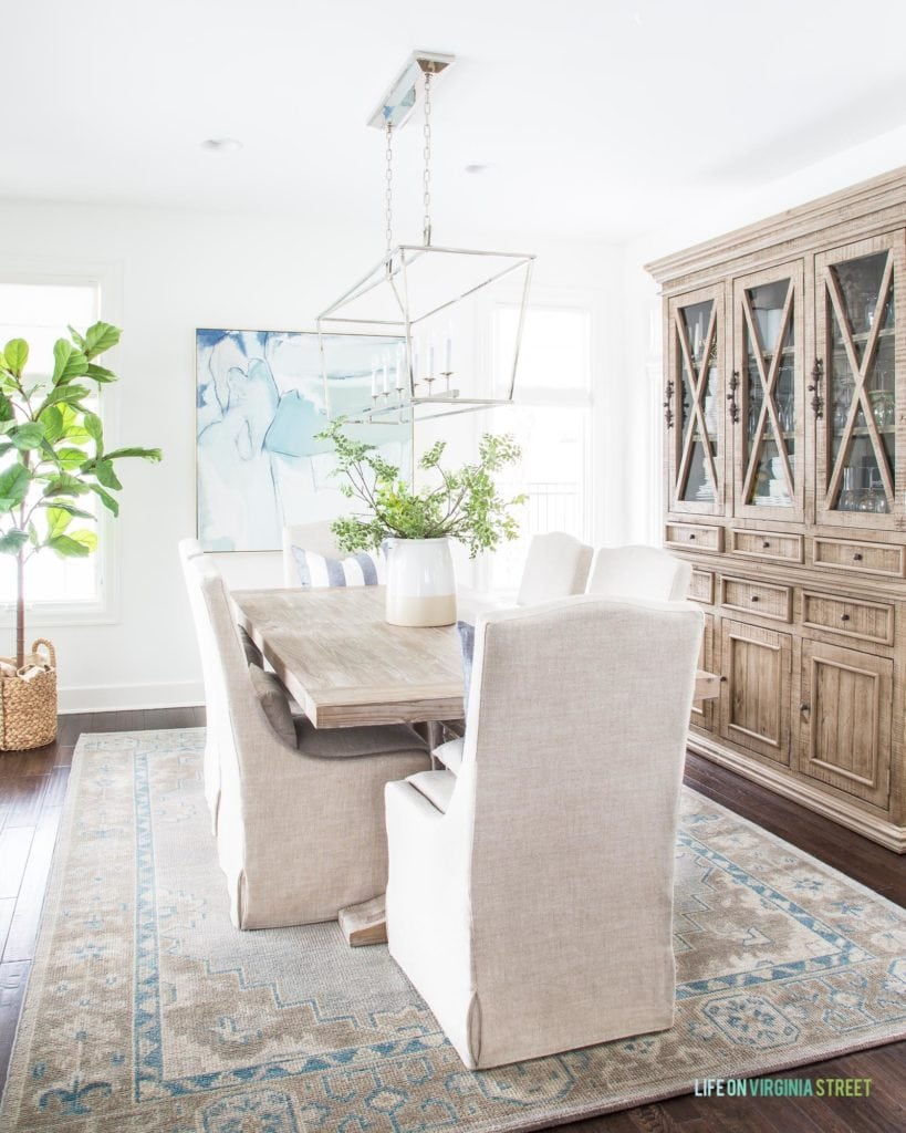 A beautiful coastal inspired dining room with linen dining chairs, abstract blue and white art, a reclaimed wood hutch, faux fiddle leaf fig tree, a wood dining table and more. Love these simple winter decor updates!