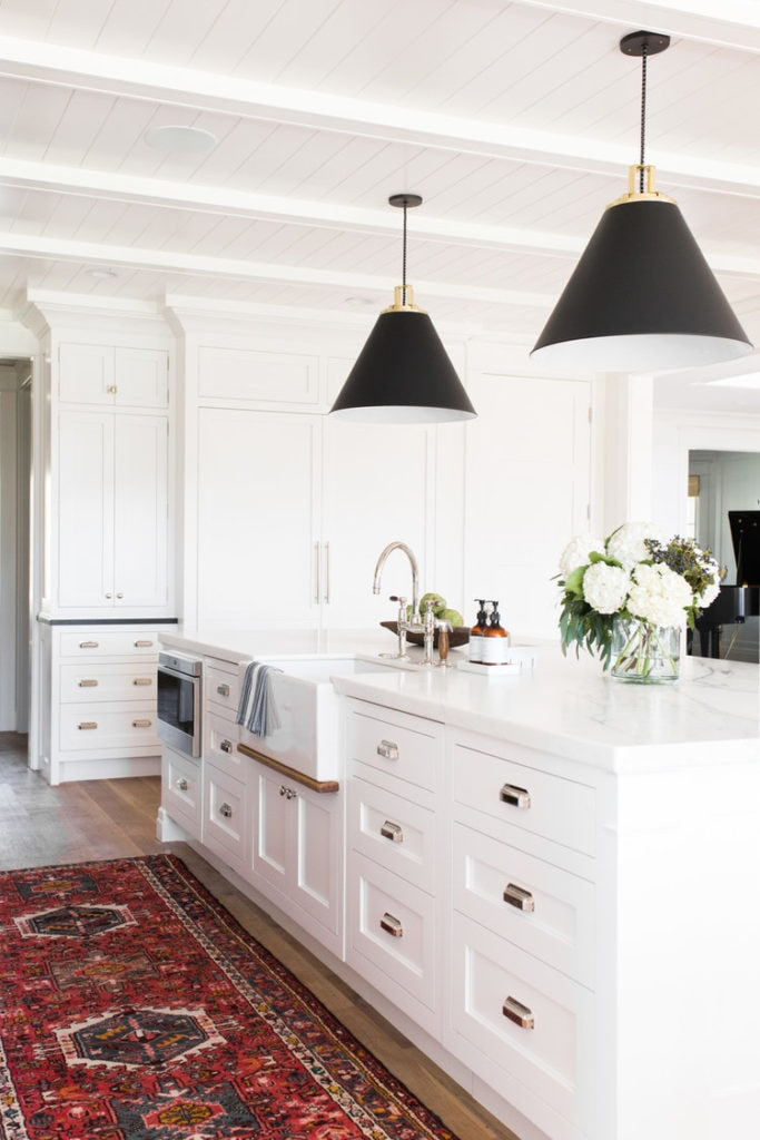 A mostly white kitchen with a red ornate rug and black lights hanging over the island.