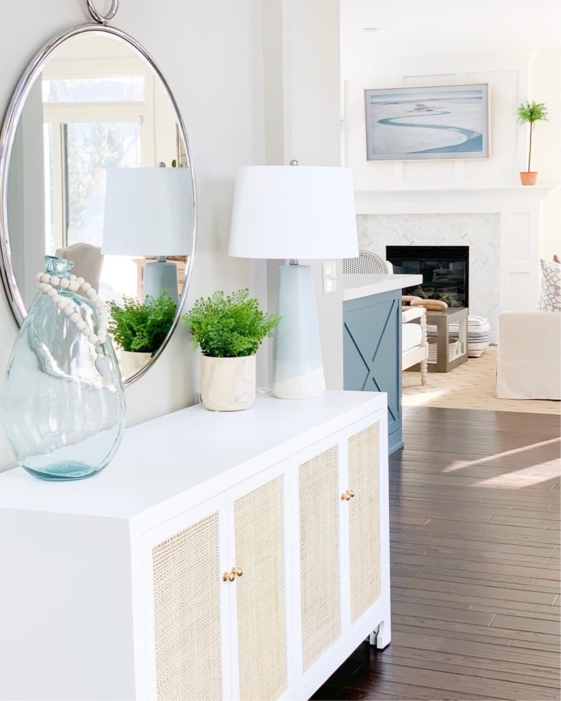 A beautiful dipped ceramic table lamp on a white and cane console table in a coastal inspired entryway. This post has a great variety of stylish table lamps and bedside lamps that work well for all budgets!