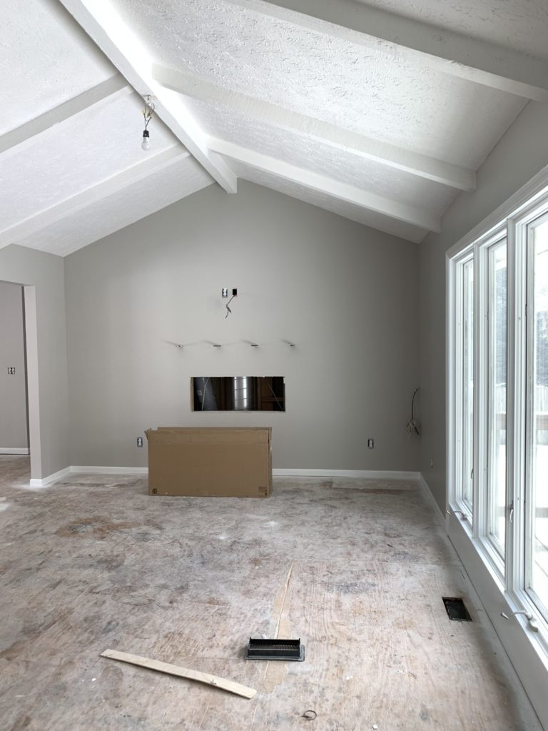 A renovated living room with a white ceiling with beams and walls painted Sherwin Williams Agreeable Gray.