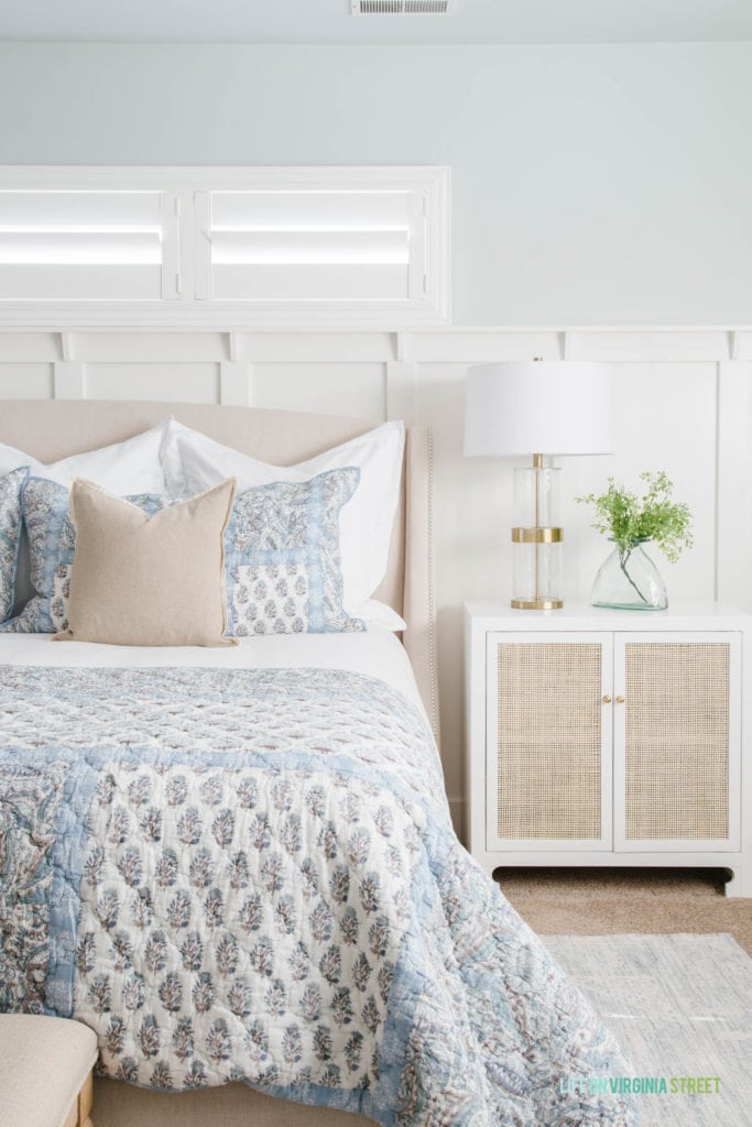 A bedroom with Sherwin Williams Sea Salt walls, a white and cane nightstand, a gold and glass lamp, blue paisley bedding and touches of greenery.