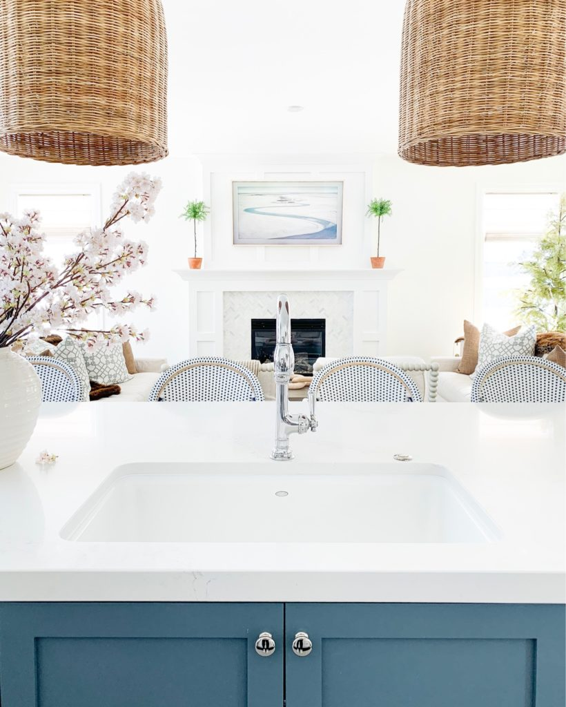 A kitchen sink view with a blue island and basket pendant lights. All made fresh with faux cherry blossom stems for spring!