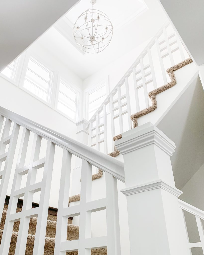 Entryway staircase painted in Benjamin Moore Simply White. Walls are an eggshell finish and the trim is semi-gloss. I love the orb chandelier and the interesting pattern on the staircase railings!