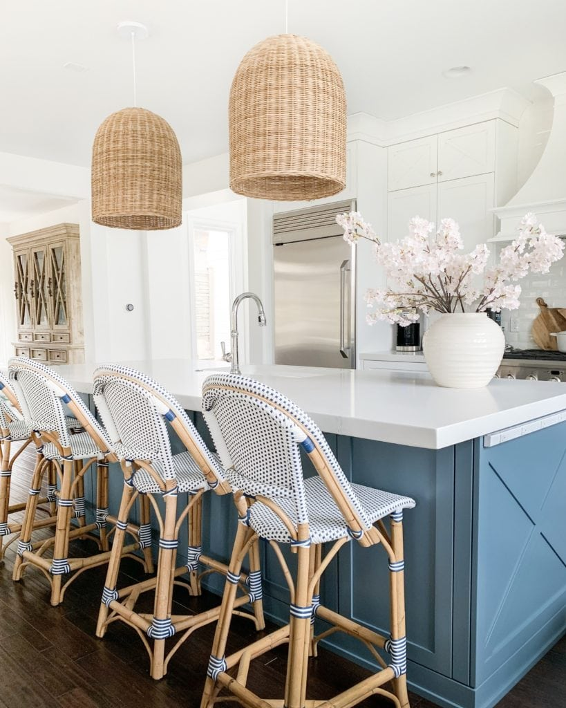 A pretty kitchen with a blue island, white cabinets, navy blue and white bistro counter stools, woven basket pendant lights, and faux pink cherry blossom stems!