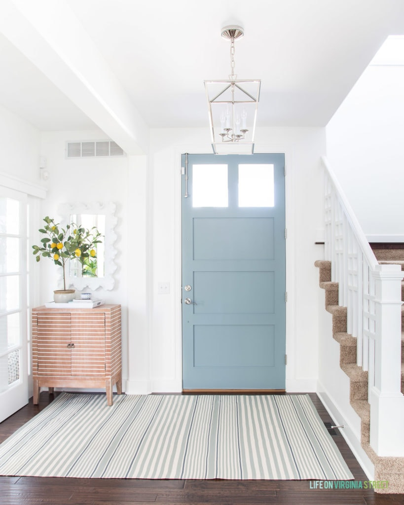 A beautiful entryway with a coastal vibe. Includes white walls, a blue gray interior painted door, striped rug, striped wood cabinet, a faux lemon tree topiary and a chrome lantern pendant light.