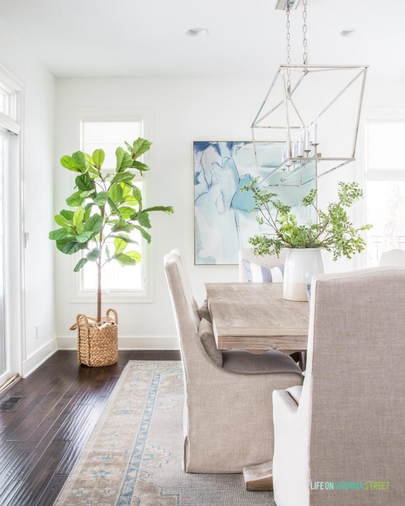 A coastal dining room with linen chairs, reclaimed wood dining table, blue abstract art, a chrome Darlana linear chandelier, hand knotted rug, faux fiddle leaf fig tree and white walls. This post shares how to get a similar look for less in your own home!