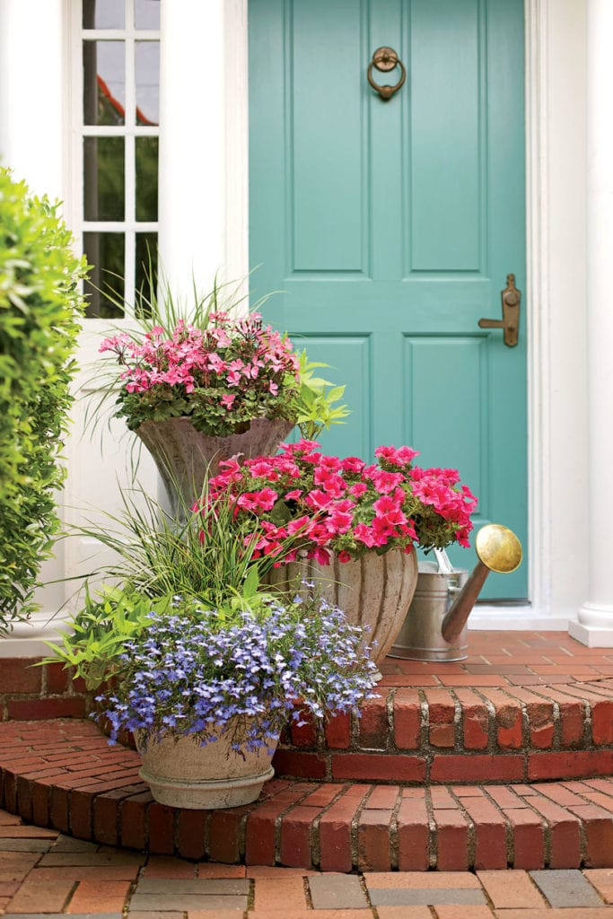 Summer porch planter ideas. These pink geraniums, petunias, and purple lobelias look so beautiful paired with the turquoise front door!