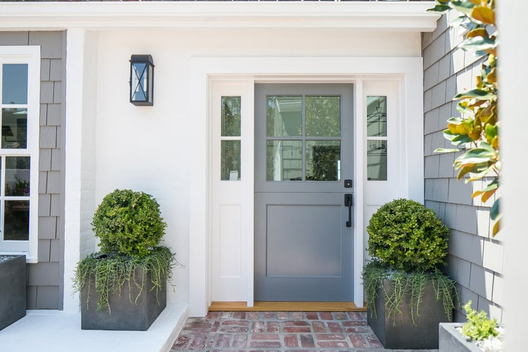 A gray modern coastal home with simple planters filled with boxwoods flanking the front door.